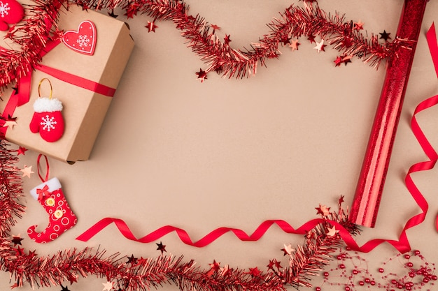 Een geschenk in ambachtelijk papier, gelegen tussen rood feestelijk klatergoud, een rood krullend lint, kleine decoratieve wanten en een kous voor snoep. humeur. kerstgeest.