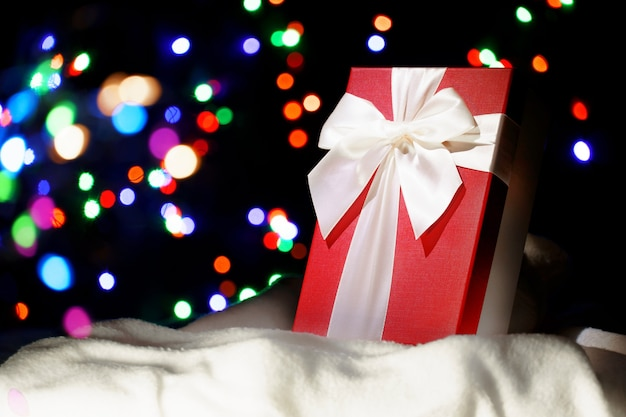 Een geschenk in de sneeuw op een achtergrond van onscherpe lichten. kerst achtergrond. ansichtkaart, spandoek