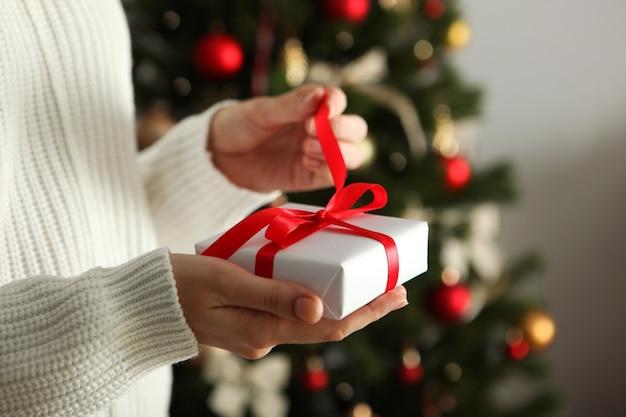 Een geschenk in handen voor kerstmis of nieuwjaar op een onscherpe achtergrond van een versierd interieur