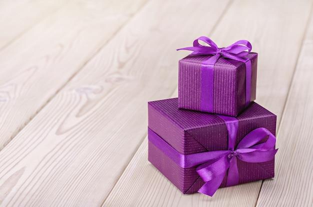Een geschenk in twee dozen verpakt in paars papier en vastgebonden met satijnen lint met strik.