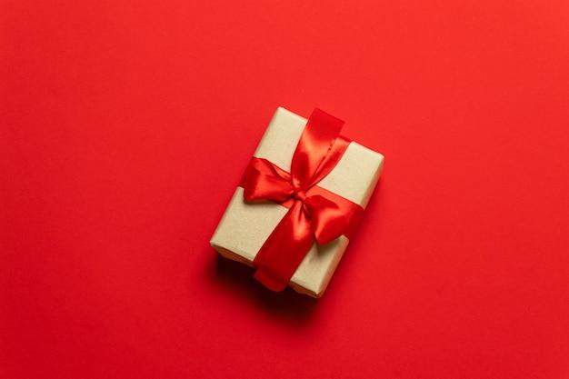Een geschenk in vak met een strik op een rode achtergrond met hart. het concept van de dag van st. valentine