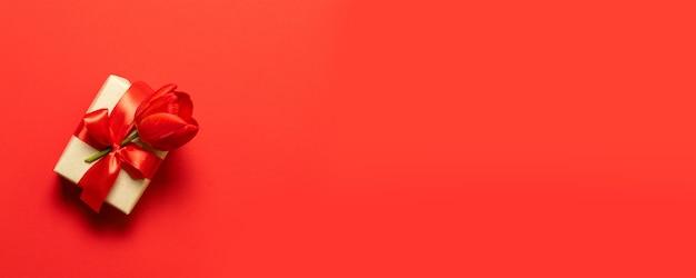 Een geschenk in vak met een strik op een rode achtergrond met hart.
