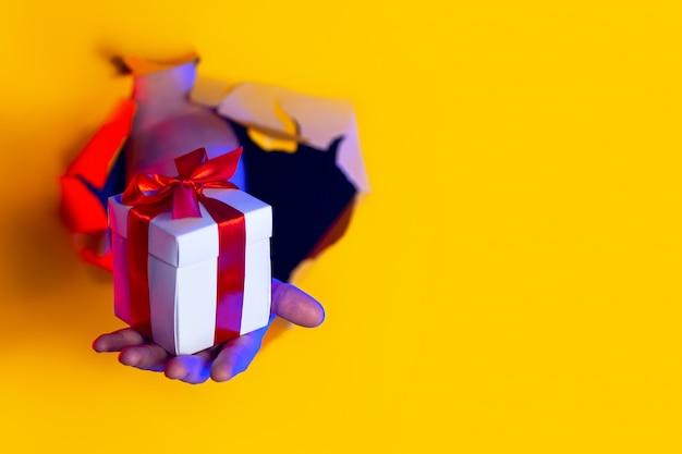Een geschenk met een rode strik in de hand komt uit een haveloos gat op geel papier achtergrond, verlicht door neonlicht