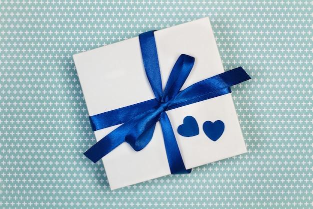 Een geschenk met papieren blauwe harten op een wit bord plus patroonachtergrond
