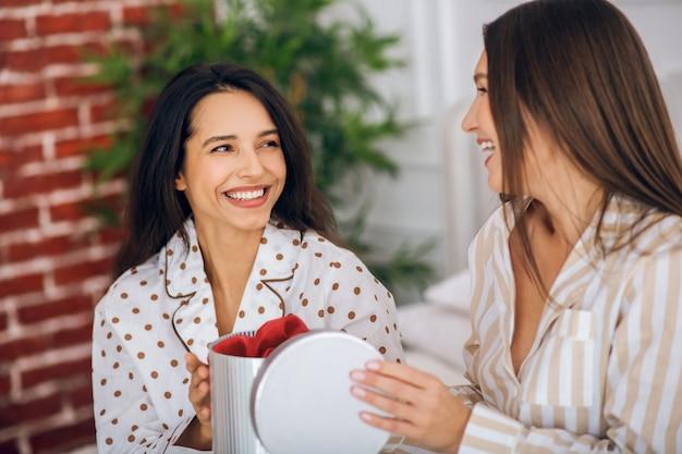 Een geschenk. twee jonge meisjes in pyjama's openen de geschenkdoos en kijken gelukkig