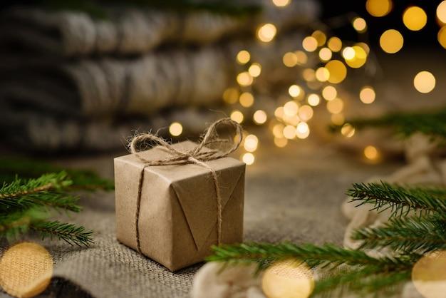 Een geschenk verpakt in ambachtelijk papier, geschoten met selectieve aandacht tegen een achtergrond van slingerlichten en kerstboomtakken
