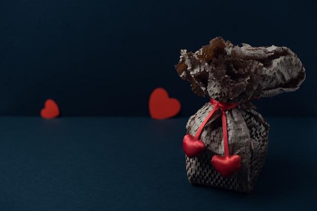 Een geschenk verpakt in kraftpapier met rood lint en rode harten op de donkere achtergrond