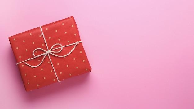 Een geschenk verpakt in rood ambachtelijke polka dot papier op een roze achtergrond.