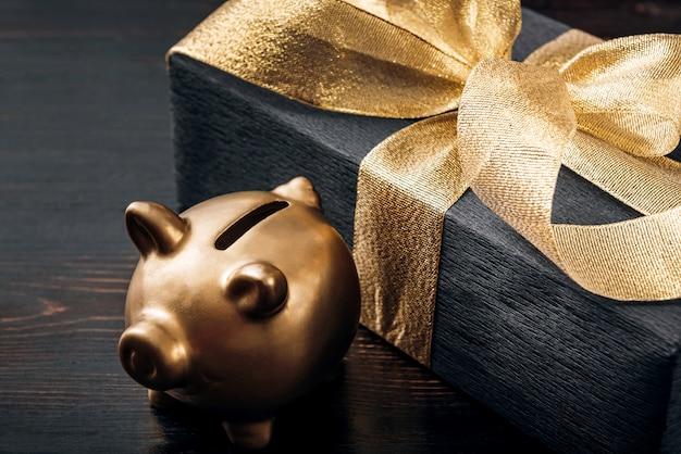 Een geschenk verpakt in zwart papier en gebonden met een gouden lint ernaast staat een gouden spaarvarken