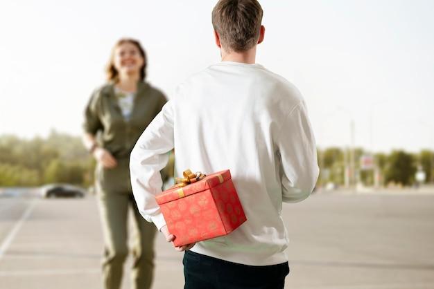 Een geschenkdoos achter de rug houden om een verrassingscadeau voor mannen te geven