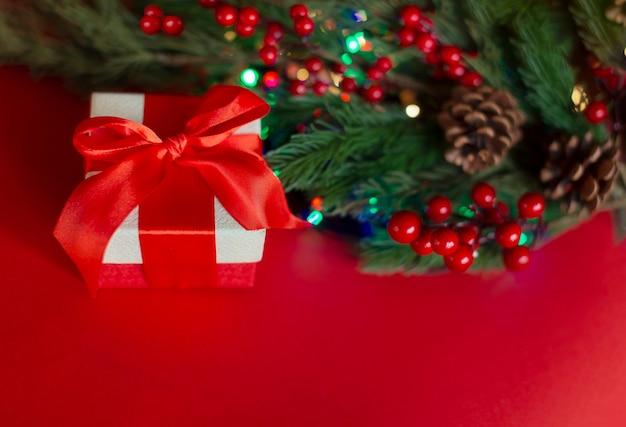 Een geschenkdoos met een rood lint en een sparrentak