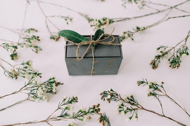 Een geschenkdoos omlijst door takken en bladeren op een witte achtergrond