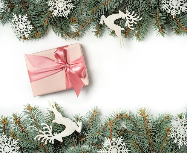 Een geschenkdoos tussen twee rijen kerstboomtakken versierd met sneeuwvlokken en hertenbeeldjes.