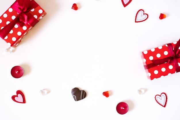 Een geschenkframe met een rode strik, kaarsen, glas en vilt harten op een witte achtergrond