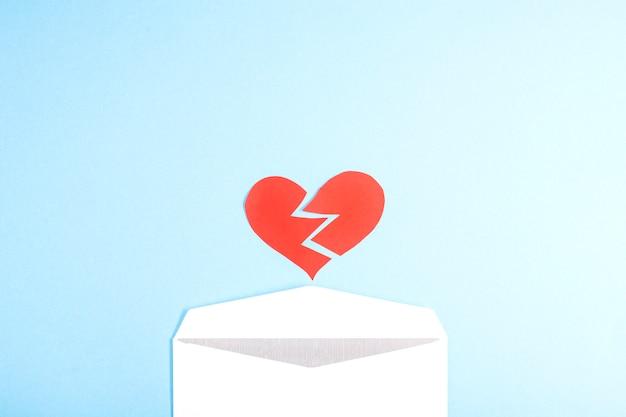 Een gescheurd rood hart valt uit een envelop op een blauwe tafel. plat leggen