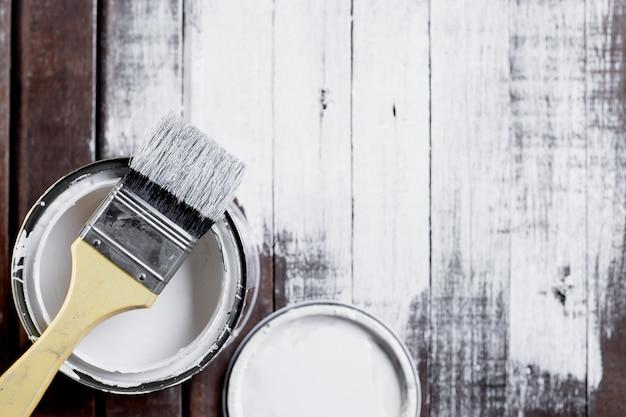 Een geschilderde borstel rust op een wit geschilderde houten vloer.