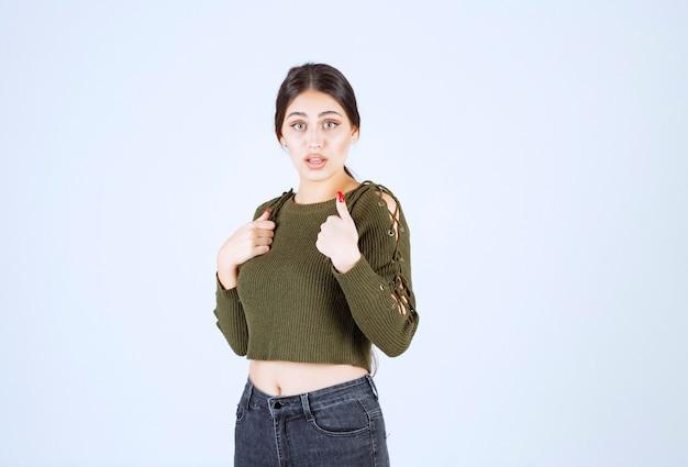 Een geschokt vrouwenmodel dat vingers naar zichzelf wijst op een witte achtergrond.