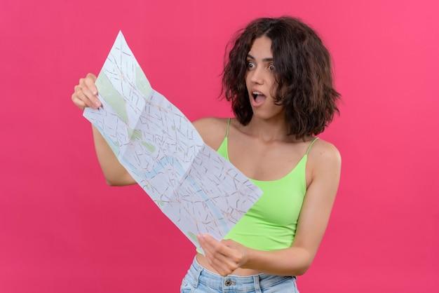 Een geschokte jonge vrouw met kort haar in een groene crop top die verrassend met open mond naar de kaart kijkt