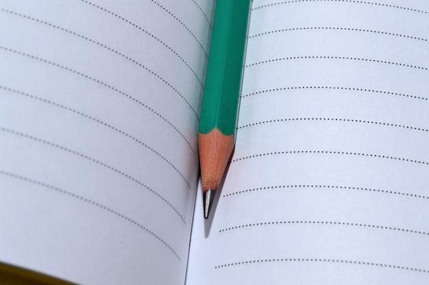 Een geslepen potlood ligt op een open notitieboekje. detailopname.