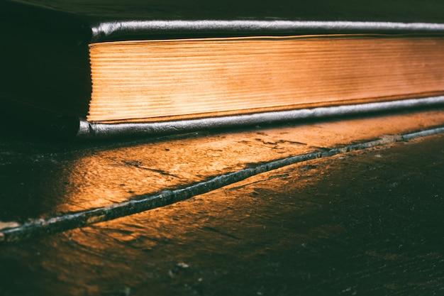 Een gesloten boek met een gouden rand op een oude zwarte houten tafel