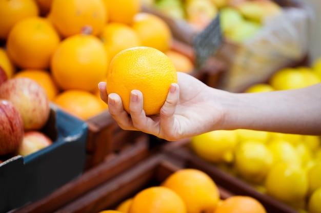 Een gesloten hand kiest sinaasappelen op de plank in een groentewinkel