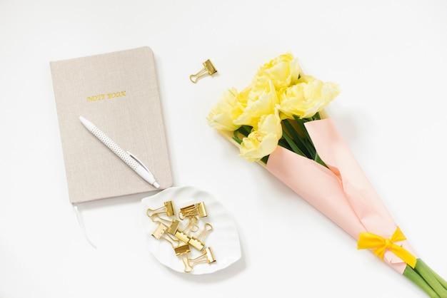 Een gesloten notitieboek met een beige kaft en een pen erop, een boeket van lente gele tulpen op een witte achtergrond. werkruimte op kantoor. geschenk aan een vrouw op het werk
