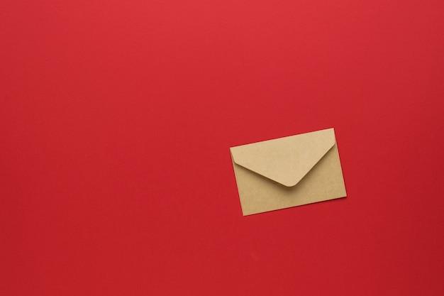 Een gesloten papieren envelop op een felrode achtergrond. plat leggen.