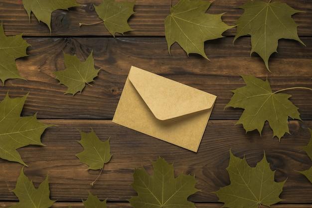 Een gesloten postenvelop en esdoornbladeren op een houten ondergrond. correspondentie.