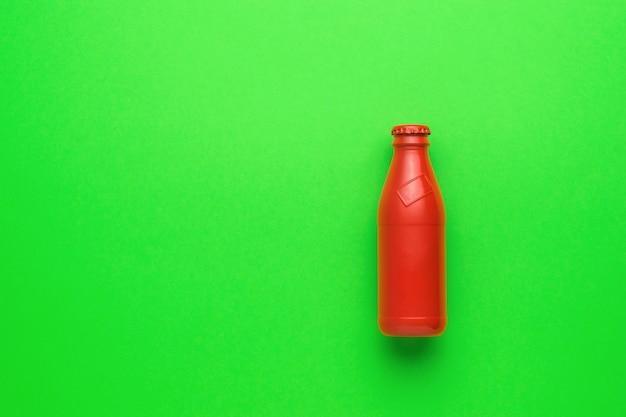 Een gesloten rode glazen fles op een heldergroene achtergrond. het concept van verfrissende drankjes.