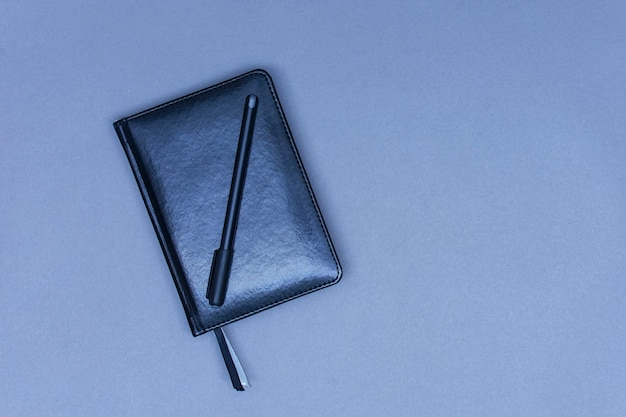 Een gesloten zwart lederen notitieboekje ligt op tafel met een pen voor notities.