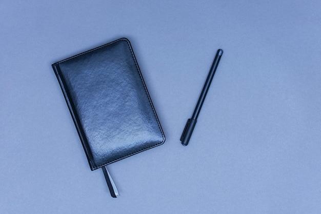 Een gesloten zwartleren dagboek ligt op een tafel met een pen voor notities.