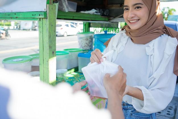 Een gesluierd straatverkopermeisje levert es campur verpakt in een plastic zak aan de koper