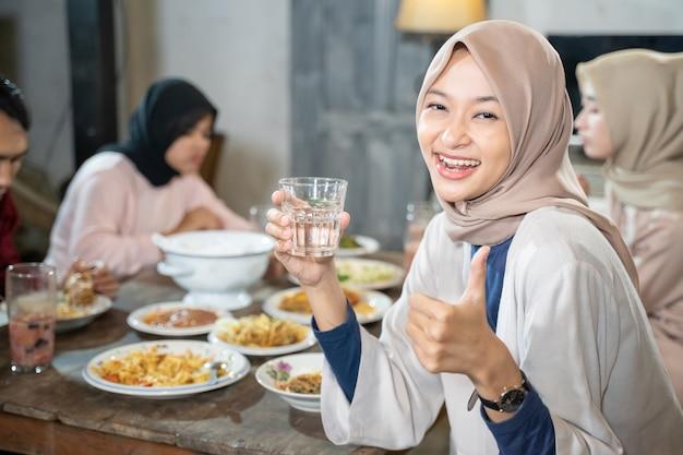 Een gesluierde vrouw lacht naar de camera met duimen omhoog terwijl ze een glas vasthoudt om snel te breken