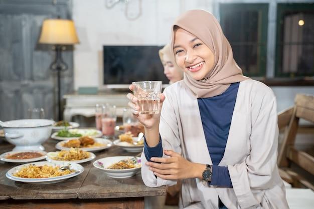 Een gesluierde vrouw lacht naar de camera met een glas om samen het vasten te verbreken