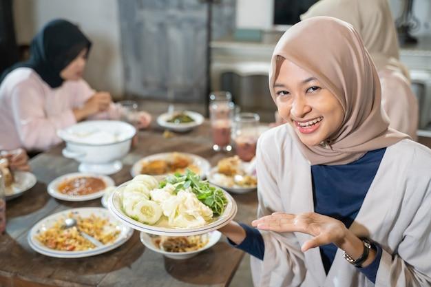 Een gesluierde vrouw lacht naar de camera met handgebaren terwijl ze een bord groenten vasthoudt