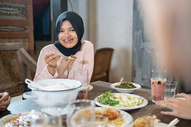 Een gesluierde vrouw lacht terwijl ze een lepel gebruikt als ze op het punt staat voedsel te eten