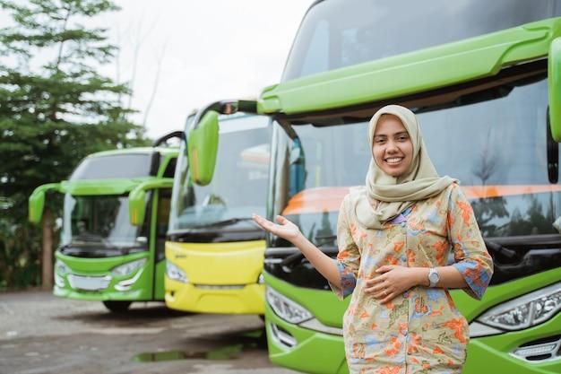 Een gesluierde vrouwelijke busbemanning die met handgebaren glimlacht en iets aanbiedt tegen de achtergrond van de busvloot