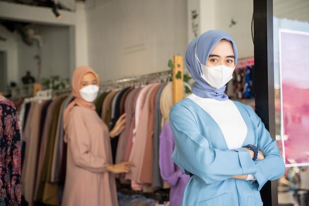 Een gesluierde zakenvrouw die een masker draagt met gekruiste armen terwijl ze staat