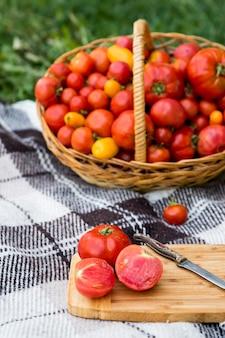 Een gesneden tomaten op een plank. oogsten in de herfst. tegen de achtergrond van een grote mand met tomaten.