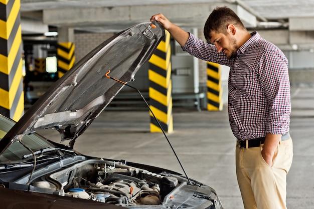 Een gespannen en gefrustreerde jonge chauffeur staat naast een kapotte auto en kijkt onder de motorkap op de parkeerplaats.