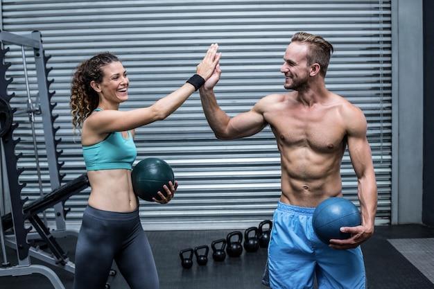 Een gespierd paar dat high five geeft