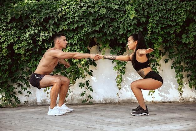 Een gespierde atleten training in het park. gymnastiek, training, flexibiliteit van fitnesstraining. zomerstad in zonnige dag op achtergrondveld. actieve en gezonde levensstijl, jeugd, bodybuilding.