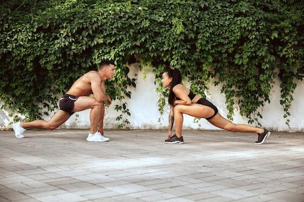 Een gespierde atleten training in het park. gymnastiek, training, flexibiliteit van fitnesstraining.