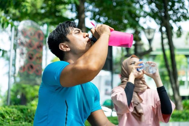 Een gespierde man en een meisje in een sluier drinken met een fles uit de dorst tijdens hun buitensportvakantie in het park