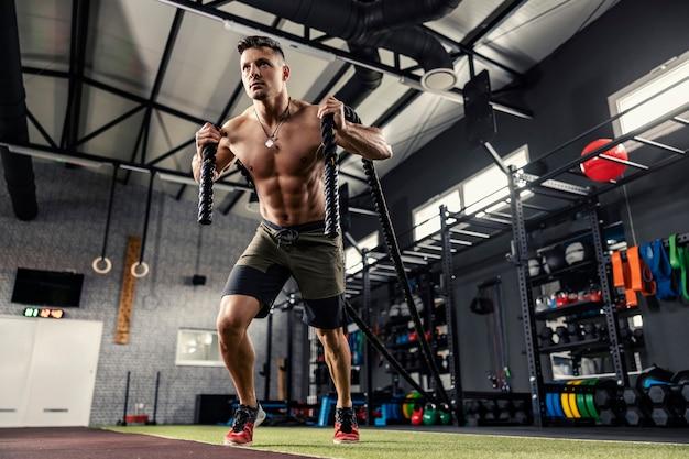 Een gespierde man zonder shirt trekt aan een touw in een moderne sportschool met apparatuur.