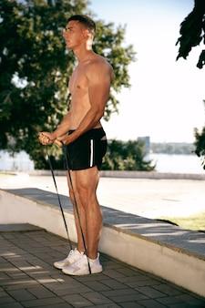 Een gespierde mannelijke atleet training in het park. gymnastiek, training, flexibiliteit van fitnesstraining. zomerstad in zonnige dag op achtergrondveld. actieve en gezonde levensstijl, jeugd, bodybuilding.