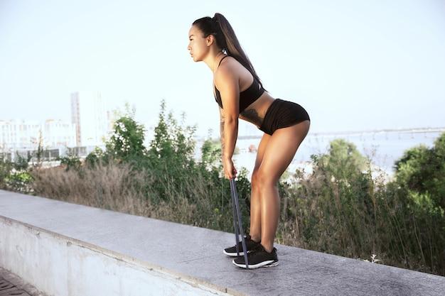 Een gespierde vrouwelijke atleet training in het park. gymnastiek, training, flexibiliteit van fitnesstraining. zomerstad in zonnige dag actieve en gezonde levensstijl, jeugd, bodybuilding.