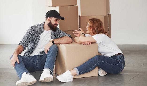 Een gesprek voeren. gelukkig paar samen in hun nieuwe huis. conceptie van verhuizen