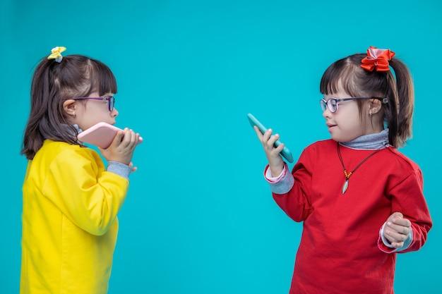 Een gesprek voeren. twee tweelingzusjes met het syndroom van down die mobiele telefoons dragen en functies gebruiken