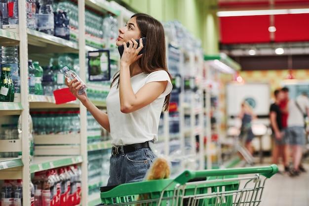 Een gesprek voeren via de telefoon. vrouwelijke shopper in vrijetijdskleding in de markt op zoek naar producten.